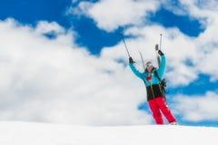 女孩freeride滑雪者,培养他的在下降前的手从Th 图库摄影