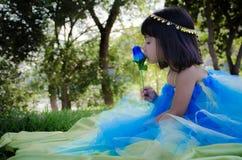 女孩kissin蓝色玫瑰 免版税库存照片
