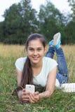 女孩llying在使用的12-14岁智能手机下 库存照片