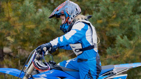 女孩mx骑自行车的人-土自行车的摩托车越野赛竟赛者在体育轨道 图库摄影
