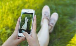 女孩photographes和她的在运动鞋的腿在电话 免版税库存图片