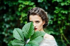 女孩Portreit有葡萄叶子的在她的手上 库存照片