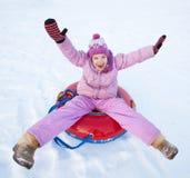 女孩sledding在冬天小山 库存照片