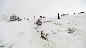 女孩sledding在雪小山下 影视素材