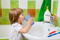 女孩toothbrushing少许嘴的冲洗 图库摄影