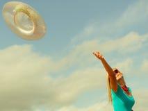 女孩trowing的帽子在海滩 免版税库存照片