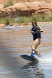 女孩wakeboarding湖的powe 免版税库存图片