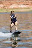 女孩wakeboarding湖的powe 免版税库存照片