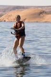 女孩wakeboarding湖的powe 免版税图库摄影