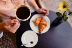 女孩whith coffe和新月形面包 免版税库存图片