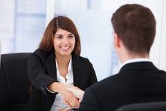 女实业家与伙伴握手在办公室 免版税库存照片