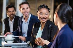 女实业家与同事握手 免版税库存图片