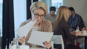 女实业家与在咖啡店的文件一起使用 股票视频