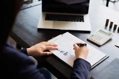 女实业家与在木桌上的收入报告文件一起使用 E 免版税库存图片