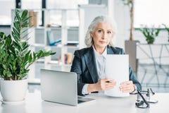 女实业家与文件和膝上型计算机一起使用,当坐在工作场所在办公室时 库存图片