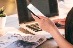 女实业家与智能手机、膝上型计算机和报纸一起使用在工作场所在办公室 图库摄影