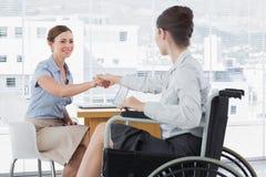 女实业家与残疾同事握手 免版税库存照片