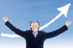 女实业家与箭头云彩的成功姿态 库存图片