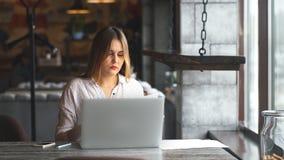 女实业家与膝上型计算机和检查一起使用在咖啡馆的本文 股票录像