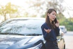 女实业家中止一辆汽车和谈话在她的busi的电话 免版税库存照片