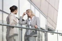 年轻女实业家争论与女性同事在办公室栏杆 库存图片