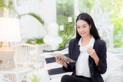 年轻女实业家亚洲开会在看片剂和拿着咖啡的桌上 免版税库存照片