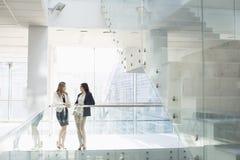 女实业家交谈反对栏杆在办公室 免版税库存照片