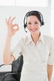 女实业家佩带的耳机,当打手势好签到办公室时 免版税图库摄影
