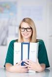 女实业家佩带的玻璃,当拿着黏合剂在书桌时 库存照片