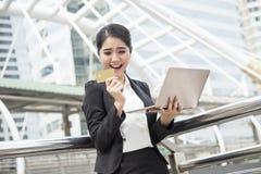 女实业家使用计算机的和信用卡为互联网开户 图库摄影