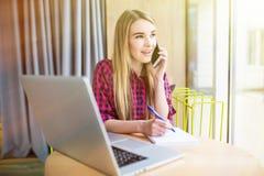 年轻女实业家侧视图画象有企业电话在办公室,她的工作场所,写下一些信息 免版税库存图片