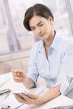 女实业家办公室smartphone使用 免版税库存图片