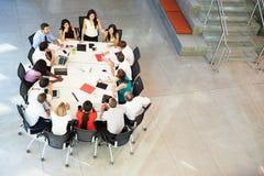 女实业家发言在会议室表附近 图库摄影
