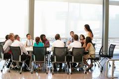女实业家发言在会议室表附近 免版税库存照片