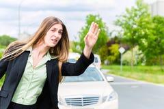 年轻女实业家呼叫请求出租汽车 库存照片