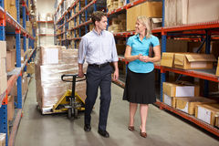 女实业家和同事在配给物仓库里 免版税图库摄影