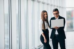 女实业家和商人在膝上型计算机站立和谈论项目在空的办公室内部窗口里有城市视图 库存照片