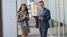女实业家和商人外面与手机和片剂个人计算机一起使用。 免版税库存图片