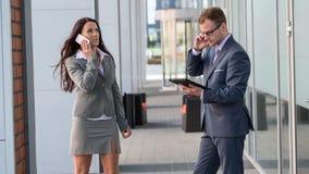 女实业家和商人外面与手机和片剂个人计算机一起使用。 库存图片