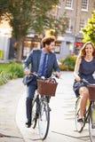 女实业家和商人骑马自行车通过城市公园 免版税库存图片