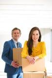 女实业家和男性同事画象有纸板箱的在新的办公室 免版税库存照片