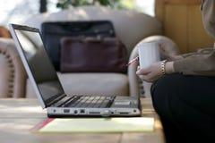女实业家咖啡膝上型计算机 库存照片