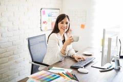 女实业家喝咖啡在她的书桌 免版税图库摄影