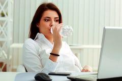 年轻女实业家喝在她的工作场所的水 免版税库存图片