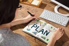 女实业家图画在笔记本的计划图 免版税库存照片