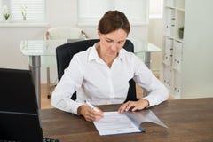 女实业家在书桌的读书文件 图库摄影