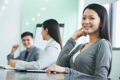 年轻女实业家在会议的看照相机 图库摄影