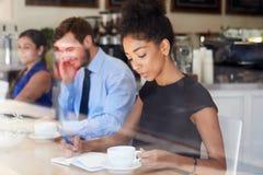 女实业家在咖啡店的文字笔记 免版税图库摄影