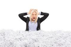 年轻女实业家在堆黏附了切细的纸 图库摄影