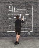 女实业家在墙壁上的图画迷宫 免版税库存图片